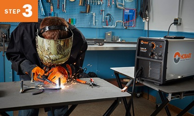 Welder welding metal with Hobart Handler 125 to his right