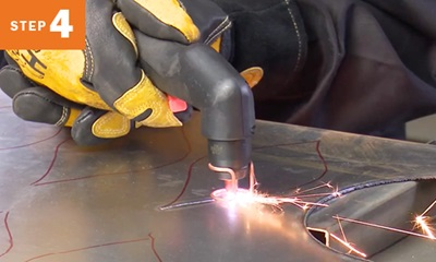 cutting out a pattern traced on metal with a plasma cutting torch