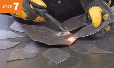 MIG welding metal pieces for a sunflower yard art project
